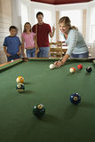 Family Playing Pool in Rec Room. Woman playing pool with family in background. Vertically framed shot Royalty Free Stock Image