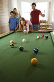 Family Playing Pool in Rec Room. Girl playing pool with family in background. Vertically framed shot Stock Photo