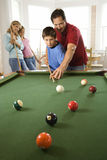 Family Playing Pool in Rec Room. Man and boy playing pool with woman and girl in background. Vertically framed shot Stock Photo
