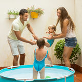 Family playing in pool at terrace. Cheerful happy young family of four playing in pool at terrace Royalty Free Stock Photos
