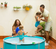 Family playing in pool at terrace. Happy smiling  young family of four playing in pool at terrace Stock Photo