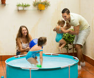 Family playing in pool at terrace. Happy young family of four playing in pool at terrace Royalty Free Stock Images