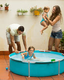 Family playing in pool at terrace. Joyful happy young family of four playing in pool at terrace Royalty Free Stock Photo