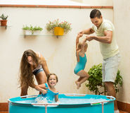 Family playing in pool at terrace. Joyful happy young family with kids playing in pool at terrace. Focus on man Royalty Free Stock Photo