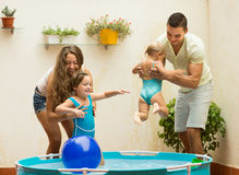 Family playing in pool at terrace. Positive young family of four playing in pool at terrace Stock Photo