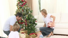 Family playing with presents around the Christmas tree at home stock video footage