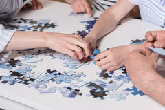 Family playing with puzzle on table at home together Stock Photos