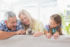 Family playing with rabbit on sofa at home Royalty Free Stock Image