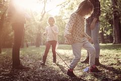Family playing with rope in park. Family playing together with rope in park stock images