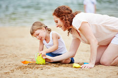 Family playing in sand of beach Royalty Free Stock Photography