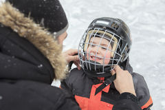 A family playing at the skating rink in winter. A father help his child to put his helmet stock image