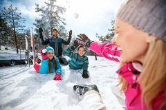 Family playing on snow in ski resort stock photography