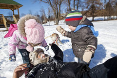 Family playing in snow. Royalty Free Stock Image