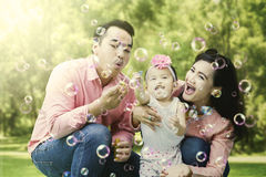 Family playing with soap bubbles at the park Stock Photo