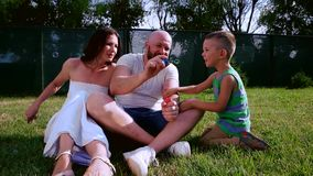 Family playing with soap bubbles sitting on the lawn, Dad keeps bubbles in hand, mother and son laughing, fun family stock video