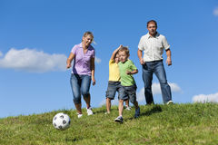 Family is playing soccer. Happy family with two little boys playing soccer in the grass on a summer meadow stock images