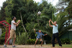 Family playing with soccer ball at park. Family playing with soccer ball against plants at park stock photos