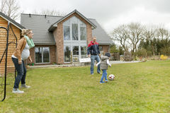 Family playing soccer in the garden Royalty Free Stock Photos