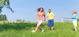 Family playing soccer on meadow in summer Stock Photo