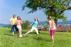 Family playing soccer on meadow in summer Stock Photos
