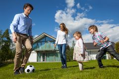 Family playing soccer outside. Family with children playing soccer on lawn near their house Royalty Free Stock Images