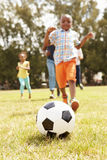 Family Playing Soccer In Park Together Stock Photos