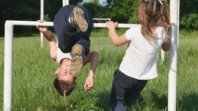 Family playing sports. Little boy and girl goes in for sports on football field on the horizontal bar sports.  stock video footage