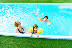 Family playing in swimming pool Royalty Free Stock Images