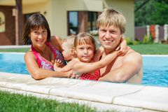 Family playing in swimming pool. Summer vacations concept. Happy family with two kids playing in blue water of swimming pool Stock Photo