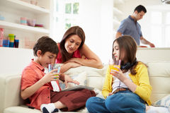 Family Playing With Tablet And MP3. Family Playing With Digital Tablet And MP3 Player Royalty Free Stock Photography
