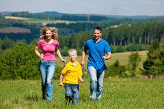 Family playing tag on meadow in summer Royalty Free Stock Image