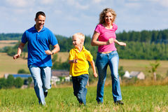 Family playing tag on meadow in summer stock photos