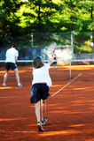 Family playing tennis. Family playing game of doubles in tennis royalty free stock image