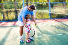 Family playing tennis on outdoor court Stock Photos