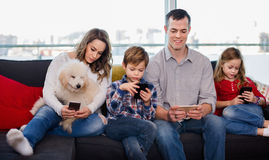 Family playing with their smartphones together at home. Young happy family playing with their smartphones together at home royalty free stock image