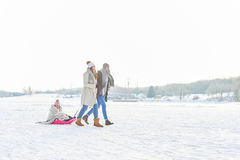 Family playing toboggan on the snow Stock Image