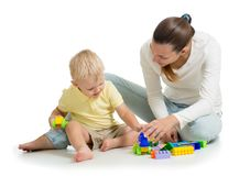 Family playing together. Mom and son play building block toys. Mother and child sitting on the floor. Isolated on white royalty free stock photography