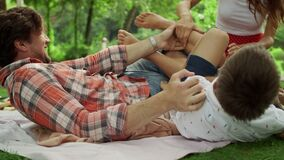 Family playing together in summer park. Parents tickling children outdoors