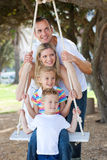 Family playing together with a swing Royalty Free Stock Photos