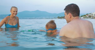 Family playing with toy frog in the sea stock footage