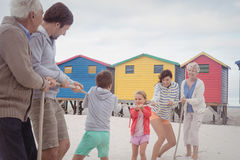 Family playing tug of war at beach Stock Photo