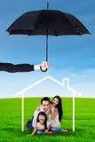 Family playing under house icon and umbrella Stock Photos