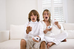 Family playing video games. Brother and sister playing video game on white sofa Stock Images