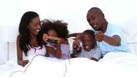 Family playing video games on bed. Family playing video games together on a bed at home stock video footage