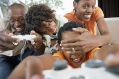 Family playing with video games console at home, mother covering son's (7-10) eyes, smiling Stock Image