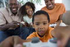 Family playing video games console on sofa at home, smiling, front view (differential focus) Stock Image