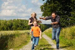 Family playing at a walk. Happy family (mother, father and kid) having a walk in the nature playing tag Stock Photo