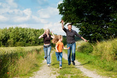 Family playing at a walk. Happy family (mother, father and kid) having a walk in the nature playing tag Royalty Free Stock Image