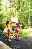 Family Playing Water Balloons. Cute little girls and their grandfather dressed in their  swimsuits making  water balloons Stock Images