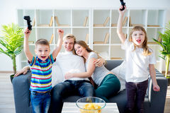 Family playing xbox. Happy family sitting on a sofa and playing xbox Royalty Free Stock Photos